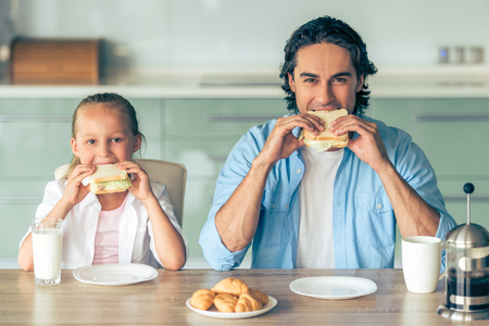 Cute little girl and her handsome father are eating sandwiches for breakfast and looking at camera, sitting in kitchen at home