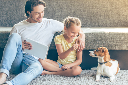 Cute little girl and her handsome father are playing with their dog and smiling while sitting on the floor at home