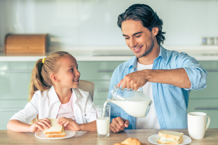mid morning: Cute little girl is eating a sandwich for breakfast, smiling and looking at her handsome father who is pouring milk, sitting in kitchen at home
