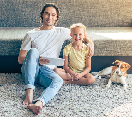 dog school: Cute little girl and her handsome father are using a digital tablet, looking at camera and smiling while sitting on the floor at home. Their funny dog is sitting near