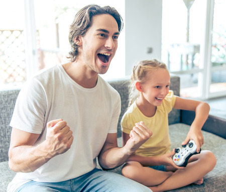 Handsome father and his cute little daughter are playing game console and smiling while sitting on couch at home. Dad is cheering for his child