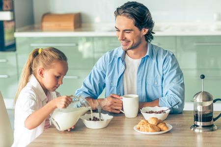 comiendo cereal: Niña linda y su apuesto padre están desayunando en la cocina de su casa. La muchacha está vertiendo leche en sus cereales mientras que el padre está sosteniendo una taza y sonriente