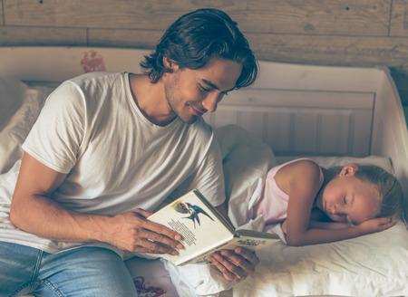 père attentionné Handsome est en train de lire un livre à sa petite fille mignonne avant lit et souriant, fille est déjà en train de dormir dans son lit à la maison