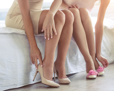 style advice: Cropped image of two beautiful girls in cocktail dresses putting on their shoes while getting ready to the party