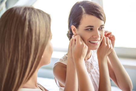 Beautiful girl is putting on her earrings and smiling, her friend is helping her while they are getting ready at home