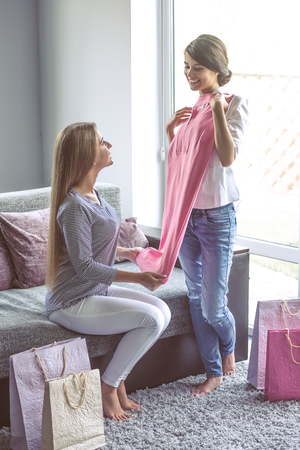 ropa casual: Two beautiful girls are examining their new clothes, talking and smiling while sitting on the couch at home