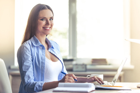 Beautiful pregnant business woman is using a laptop, writing, looking at camera and smiling while sitting at her working place at home