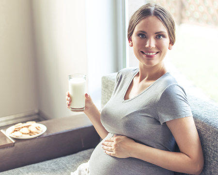 Beautiful pregnant woman is drinking milk, holding one hand on her tummy, looking at camera and smiling while sitting on the couch at home