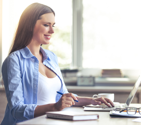 Beautiful pregnant business woman is using a laptop, holding a pen and smiling while working at home Stock Photo
