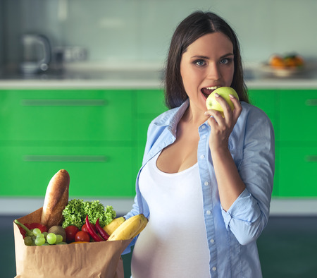 Beautiful pregnant woman is biting an apple, looking at camera and smiling while standing near the paper bag with food in her kitchen at home