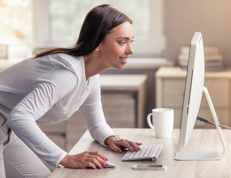 Side view of attractive business lady in stylish clothes using a computer and smiling while working in office