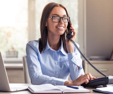 공식적인 옷 및 안경에 매력적인 비즈니스 아가씨는 전화로 얘기하고 사무실에서 일하는 동안 웃고