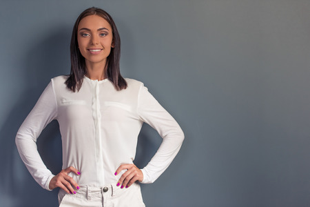 akimbo: Attractive business lady in formal clothes is looking at camera and smiling while standing akimbo on gray background