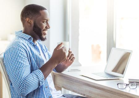 Vista laterale di bel uomo afro americano in abiti casual in possesso di una tazza e sorridente mentre seduto a tavola a casa Archivio Fotografico