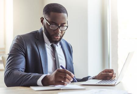 De knappe Amerikaanse zakenman van Afro in klassieke kostuum en oogglazen gebruikt laptop en maakt nota's terwijl het werken in bureau