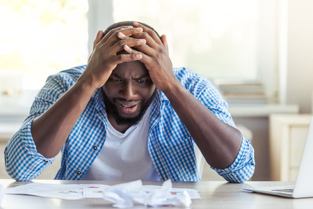 businessman working at his computer: Handsome tired Afro American businessman in casual clothes is leaning on his hands in despair while working with computer at home