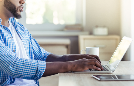 Side view of handsome Afro American man in casual clothes using a laptop while working at home, cropped