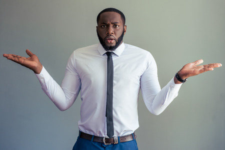 embarrassment: Handsome Afro American businessman in white classic shirt is spreading hands, looking at camera and showing embarrassment, on gray background
