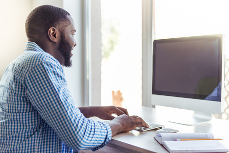 Handsome Afro American businessman in casual clothes is using a computer and smiling while working at home