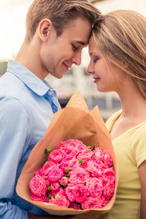 Beautiful young couple on a date leaning heads, holding flowers and smiling