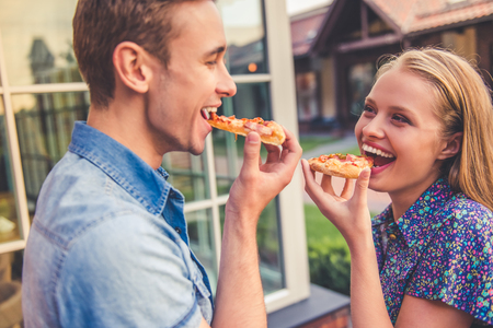 wooing: Beautiful young couple is eating pizza, looking at each other and smiling while walking outdoors
