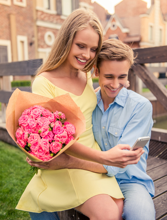 fashion clothing: Beautiful young couple is using a smart phone, holding flowers and smiling while sitting outdoors Stock Photo