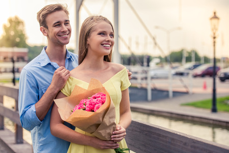 wooing: Beautiful young couple on a date is looking away and smiling. Girl is holding flowers