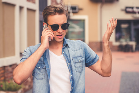 irritation: Handsome stylish guy in casual clothes and sun glasses is talking on the mobile phone and showing irritation while standing outdoors