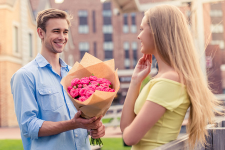 wooing: Handsome young man is presenting flowers to his beautiful girlfriend and smiling, standing outdoors Stock Photo