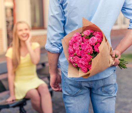 Vista trasera de la explotación agrícola del hombre joven hermoso flores a la espalda de su bella novia