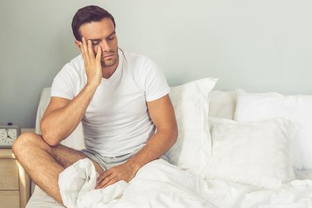 levantandose: cansado hombre guapo en camiseta blanca se apoya en su mano y sentado con los ojos cerrados en la cama al levantarse en la ma�ana