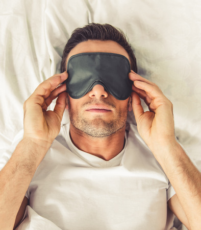 sleeping mask: Portrait of handsome man in sleeping mask lying in bed