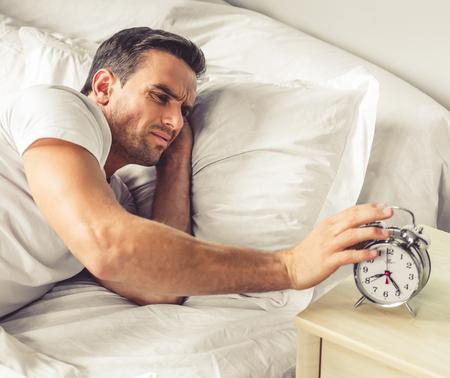 levantandose: apuesto hombre cansado es apagar un despertador al levantarse en la mañana Foto de archivo