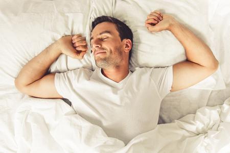그의 침대에서 자고있는 동안 웃는 잘 생긴 남자의 상위 뷰