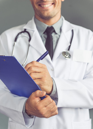 Cropped image of handsome medical doctor in white coat making notes and smiling while standing on gray background Stock Photo