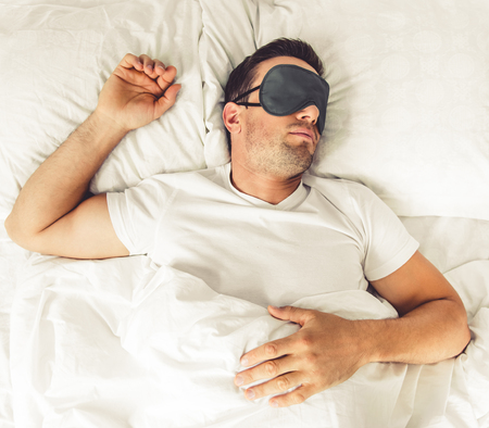 Top view of handsome man in sleeping mask in his bed at home Stock Photo