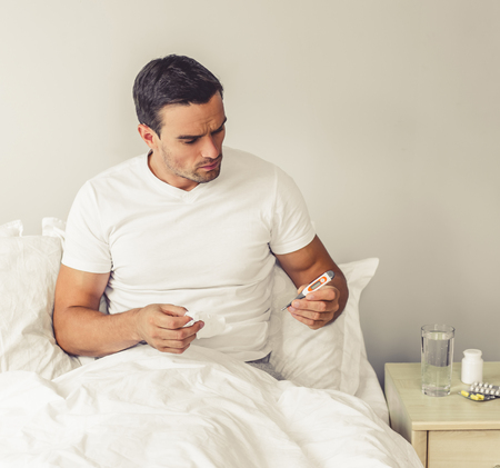 body temperature: Handsome man is having a common cold. He is holding a thermometer and paper tissue while sitting in bed at home