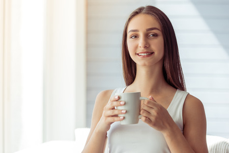 white singlet: Attractive young girl in white singlet is holding a cup, looking at camera and smiling while sitting on couch at home