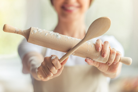 Cropped image of woman holding a wooden spoon and a rolling pin for baking, close-up