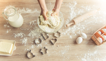 Top view of woman kneading the dough, all the ingredients and cookie cutters are near