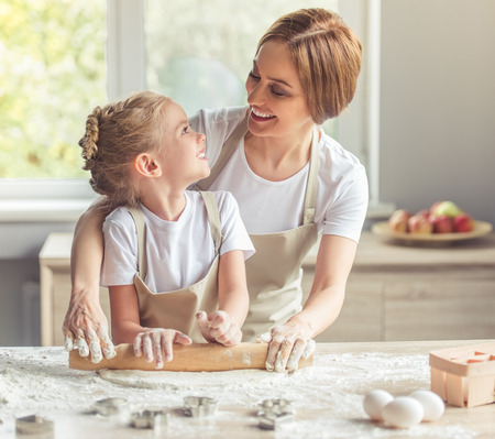 Cute little girl and her beautiful mom in aprons are looking at each other and smiling while flattening the dough using a rolling pin in the kitchen