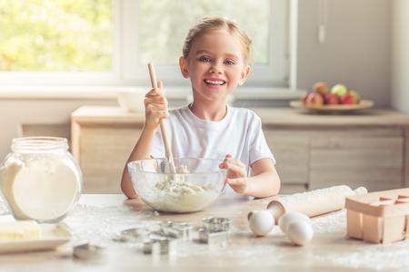 nudelholz: Nettes kleines Mädchen in die Kamera und lächelt, während er den Teig in der Küche kneten