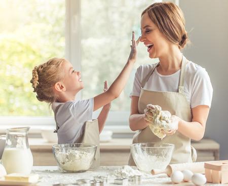 Nettes kleines Mädchen und ihre schöne Mutter in Schürzen spielen und lachen, während sie den Teig in der Küche kneten
