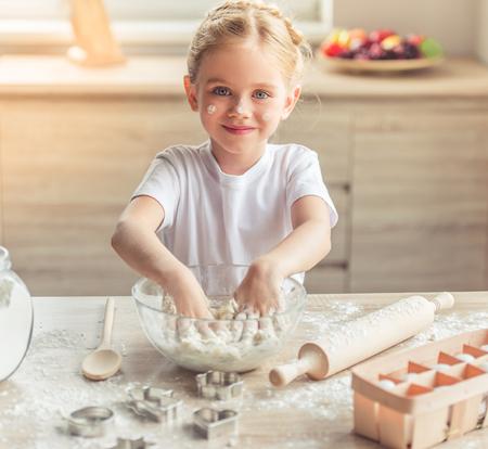 Schattig klein meisje is op zoek naar de camera en glimlachen terwijl het kneden van het deeg in de keuken Stockfoto