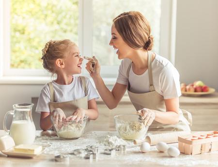 Leuk meisje en haar mooie moeder in schorten spelen en lachen tijdens het kneden van het deeg in de keuken Stockfoto