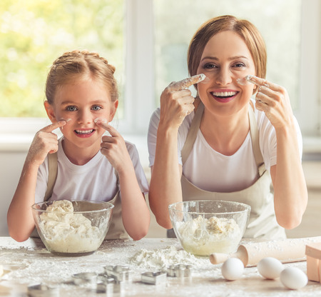 smearing: Cute little girl and her beautiful mom in aprons are looking at camera, smearing flour on their faces and smiling while kneading the dough in the kitchen Stock Photo