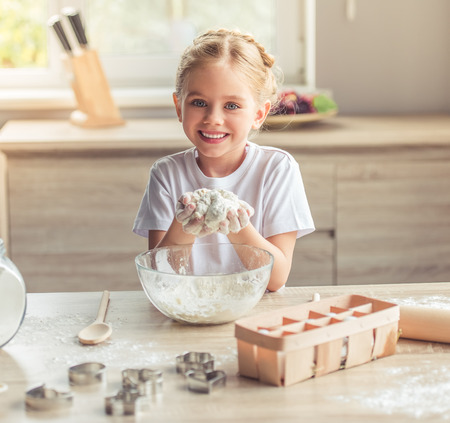 pastry cutters: Cute little girl is looking at camera and smiling while kneading the dough in the kitchen