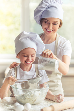 Cute little girl and her beautiful mom in aprons and cooking hats are smiling while preparing the dough for baking in the kitchen Foto de archivo