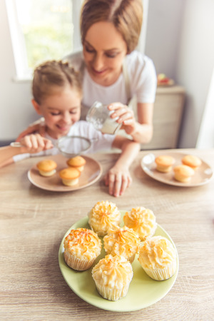 dredging: Sweet muffins on a plate, in the background beautiful woman and her cute little daughter are smiling while dredging muffins with sugar powder