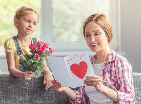 Schöne Mutter ist eine Grußkarte von ihrem süßen kleinen Tochter zu lesen und lächelnd, während auf der Couch zu Hause sitzen. Mädchen hält Blumen und Blick auf ihre Mutter photo
